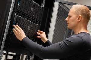 Confident male technician installing servers in enterprise datacenter for cloud hosting.