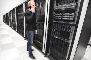 IT consultant or engineer work and solve problems in data room. Photo from a large enterprise datacenter.